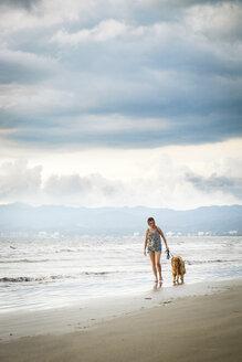 Mexico, Nayarit, Young woman walking Golden Retriever dog at the beach - ABAF02077