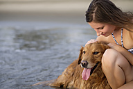 Close up of young woman in bikini stroking her Golden Retriever dog at the beach - ABAF02080