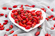 Heart-shaped bowl of goji berries on cloth - SARF02965