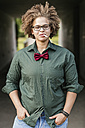 Portrait of lesbian with cigarette wearing glasses and bow tie - GDF01149