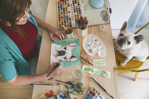 Artist painting an aquarelle of her French bulldog in her studio - RTBF00445
