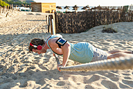 Spain, Mallorca, sportsman at the beach, pushup on rope - DIGF01382