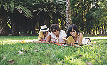Friends in park reading book and using cell phone - DAPF00362