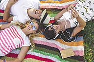 Young woman with friends lying on blanket listening to music - DAPF00365