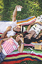 Playful friends lying on blanket in park taking a selfie - DAPF00368