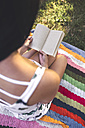 Close-up of woman sitting on blanket reading book - DAPF00380