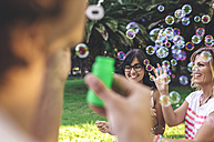 Young happy friends having fun and playing with soap bubbles in park - DAPF00389