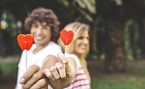 Young couple holding heart-shaped lollipops - DAPF00395