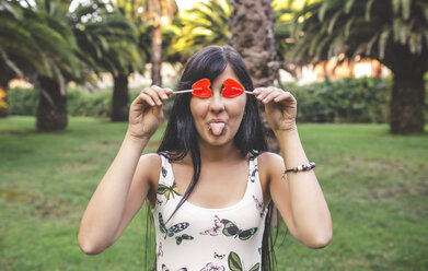 Playful young woman covering her eyes with heart-shaped lollipop - DAPF00398