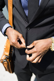 Hands of businessman buttoning jacket, close-up - GIOF01469
