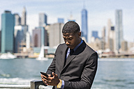 USA, Brooklyn, businessman looking at cell phone in front of Manhattan skyline - GIOF01478