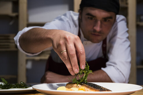 Chef decorating a slice of salmon with arugula - ABZF01370