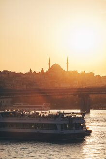 Turkey, Istanbul, view of ferry boat on Bosphorus with silhouette of mosque at sunset - BZ00352