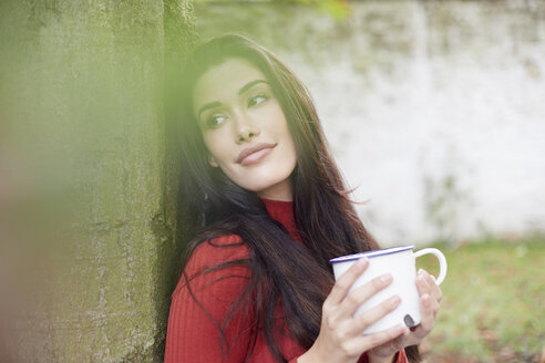 Portrait of daydreaming woman with cup of coffee leaning against tree trunk - FMKF03105