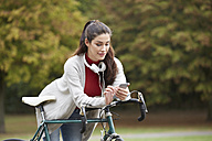 Woman with bicycle in an autumnal park text messaging - FMKF03111