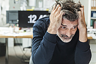 Mature man sitting in office with head in hands - TCF05172