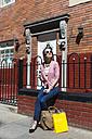 Ireland, Dublin, woman with shopping bags and coffee to go sunbathing - BOYF00590