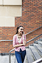 Woman standing on stairs telephoning with smartphone - BOYF00593