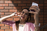 Portrait of young woman showing victory sign taking selfie with smartphone - BOYF00599