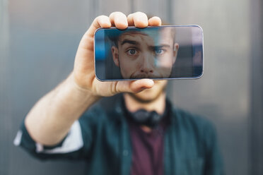 Display of smartphone showing young man pulling funny face - BOYF00629