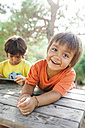 Portrait of relaxed little boy with his brother using tablet in the background - VABF00808