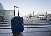 Blue suitcase at airport, airplane in background - RAEF01516
