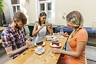 Friends sitting outdoors with coffee and cake taking cell phone pictures - AIF00377