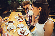 Friends sitting outdoors having coffee and cake - AIF00380