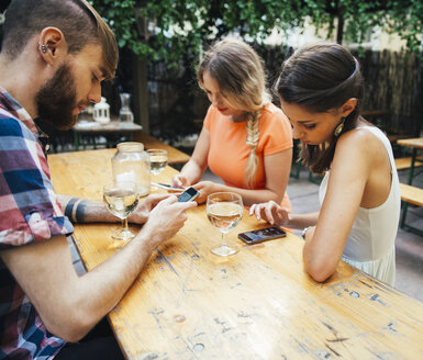 Friends using cell phones and drinking spritzer at outdoor pub - AIF00404
