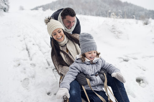 Happy family on sledge in winter landscape - HAPF00953