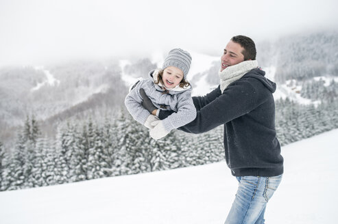 Father playing with daughter in winter landscape - HAPF00962