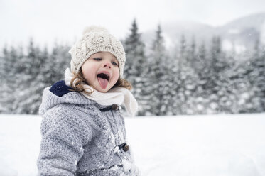 Girl in winter landscape catching snowflakes with her tongue - HAPF00971