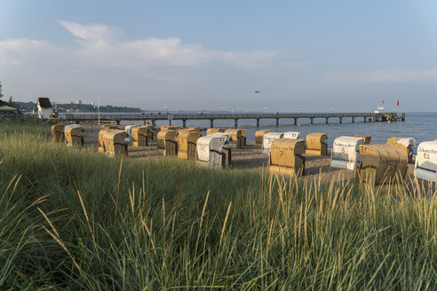 Germany, Haffkrug, view to the beach with hooded beach chairs and sea bridge in the background - PC00288