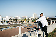 Spain, Barcelona, man standing next to bicycle looking at view - JRFF00913