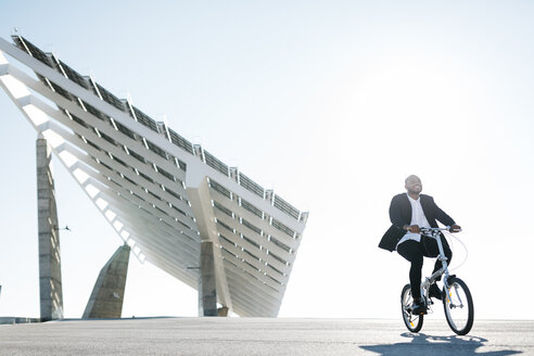 Businessman riding bicycle at solar panels - JRFF00922