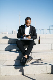 Businessman sitting on stairs with bottle of beer, notebook and laptop - JRFF00928