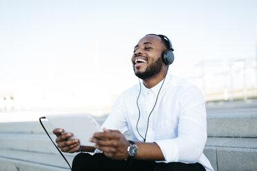 Happy man sitting on stairs wearing headphones holding tablet - JRFF00940
