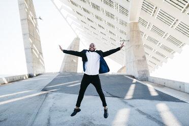 Vital businessman jumping under solar panels - JRFF00946