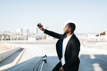 Smiling businessman with bicycle taking a selfie - JRFF00949