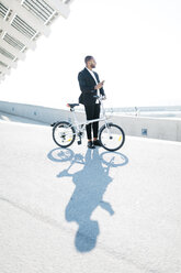 Businessman with bicycle holding cell phone - JRFF00952