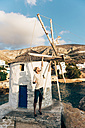 Greece, Amorgos, Aegialis, man holding the the blades of wind mill - GEMF01144