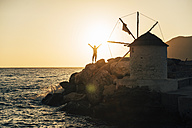 Greece, Amorgos, Aegialis, silhouette of man with arms raised near wind mill at sunset - GEMF01147