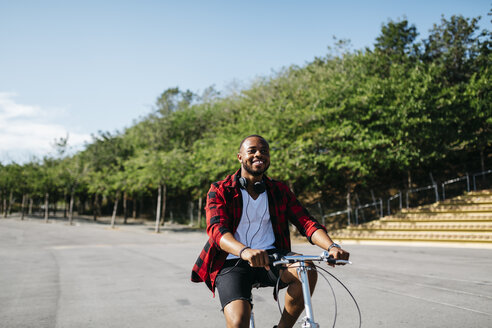 Smiling man riding bicycle through a park - JRFF00962