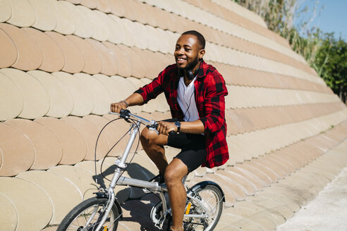 Smiling man riding bicycle - JRFF00968