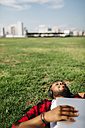 Man lying in grass with laptop listening to music - JRFF00974