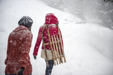 Two young women with sledges in heavy snowfall - HHF05410