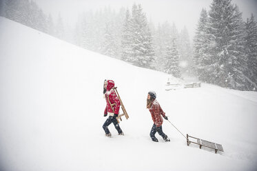Two young women with sledges in heavy snowfall - HHF05413