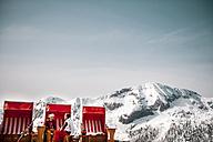 Austria, Altenmarkt-Zauchensee, couple sitting at hooded beach chair in the mountains - HHF05422