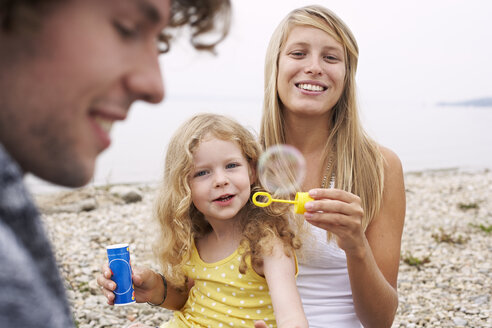 Parents with daughter at a lake blowing soap bubbles - FSF00580
