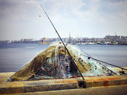 Italy, Apulia, Pile of fishing nets and rods at harbor of Gallipoli - DIKF00220